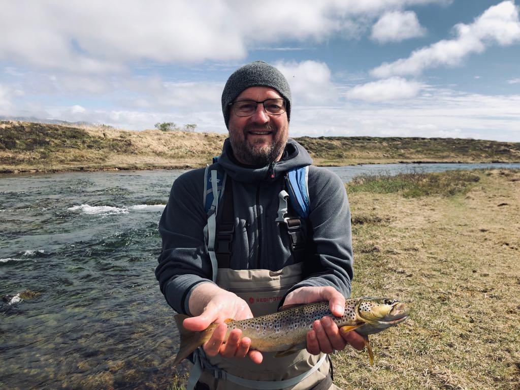 homme tenant une truite dans les mains, lors d'un voyage de pêche dans les perles du sud en islande