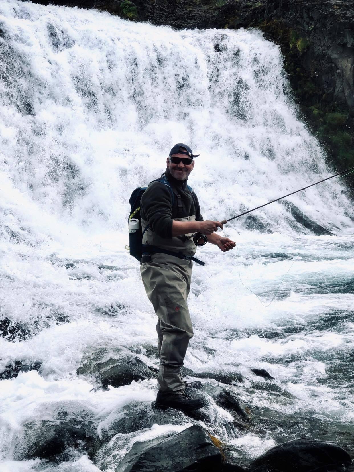 pêcheur se tenant debout près d'une cascade lors du circuit de pêche les perles du sud en islande